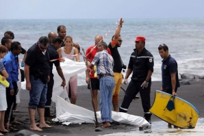 Local authorities cover the young man's body on the beach. Photo: Richard Bouhet / AFP